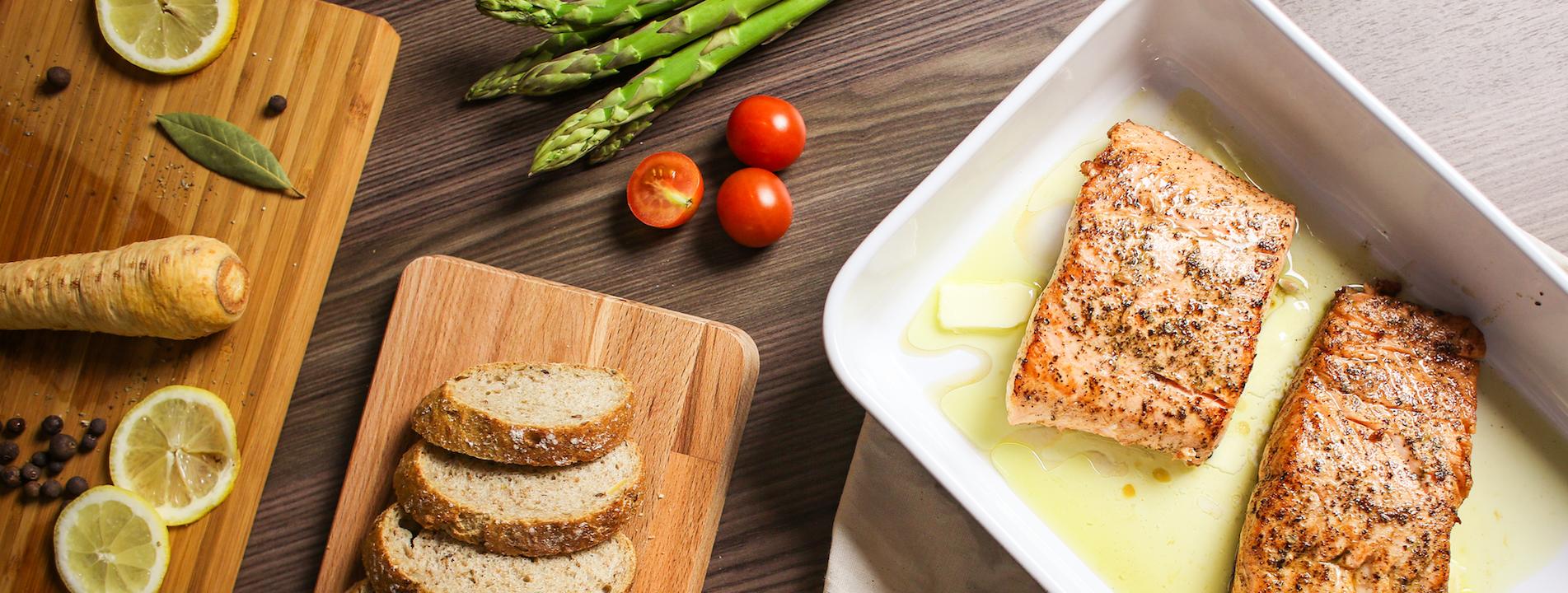 Een tafel vol met gezonde voeding en ingrediënten op snijplankjes (Gember, citroen, zalm, brood, tomaat, asperges)